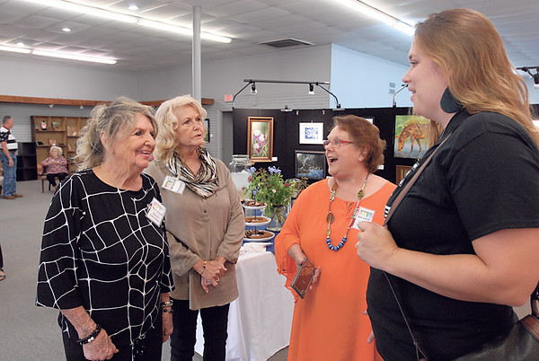 CHESLEY OXENDINE/Muskogee Phoenix<br /> (From left) Muskogee Art Guild members Gwyn LaCrone, Glenda Trammel and Sandra Willems chat with new member Marisa Pack. The Art Guild hosted a show and sale for members Friday night, drawing a crowd. Prize money was awarded to one beginner artist and one advanced artist. Rachel York won $100 for winning the beginner category while Paula Hefley won the same for the advanced category.