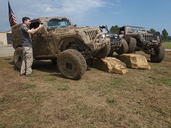 CHESLEY OXENDINE/Muskogee Phoenix<br /> Mark Busemburg chats with passenger Donetta Johnson in a muddy Jeep perched on a rock for photos at Okie Jeep Jam Saturday.