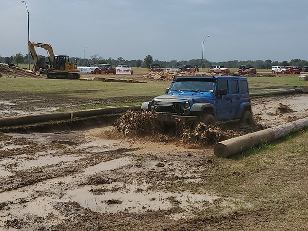 A Jeep driver plows through the mud pit at Okie Jeep Jam on Saturday at Hatbox Field.
