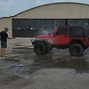 Trenton Fox cleans his Jeep after a trip through the mud pit at Okie Jeep Jam at Hatbox Field on Saturday.
