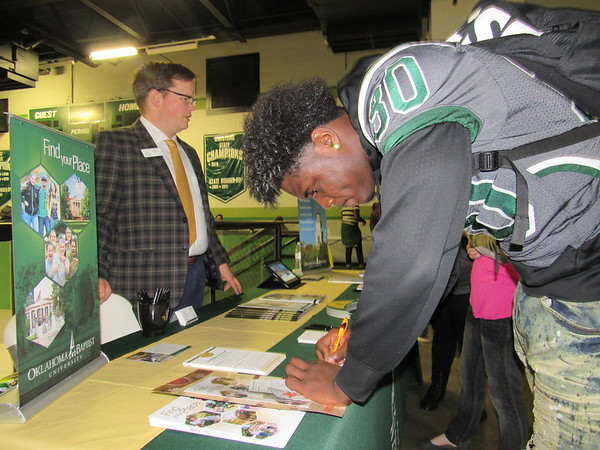 Staff photo by Cathy Spaulding<br /> Oklahoma Baptist University admissions counselor Kaleb Miears, left, stands by while Muskogee High senior Mike Edwards fills out an information card during the MHS College Fair. Juniors and seniors were to attend the fair.