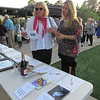 Staff photo by Cathy Spaulding<br /> Fonda Richmond, left, and Amy Bradshaw study the Moonlight and Monarchs program and silent auction items Friday evening at the Papilion event lawn. The two said they are newcomers to Muskogee and were impressed by the gala and Papilion.