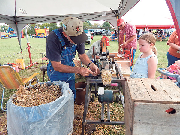 KENTON BROOKS/Muskogee Phoenix<br /> Mike Davis, left, of Dewey, makes hay bales while Kloee Holland, of Tahlequah, watches Saturday at the Fourth annual Wagoner Fall Festival and Tractor Show at Dunbar Park.