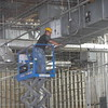 KENTON BROOKS/Muskogee Phoenix<br /> Cody Allison of Moore Electric stands on a lift to work on electrical demolition inside the old Sears store in Arrowhead Mall on Thursday. The demolition starts the project of putting in the new post office and distribution center, said Superintendent Cary Treat of Magnum Construction Inc., of Broken Arrow. Treat said the project started in mid-September and will continue until May, or for nine months, until it's completed.