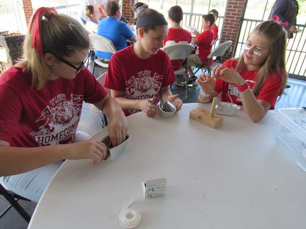 CATHY SPAULDING/Muskogee Phoenix<br /> Fort Gibson eighth-graders, from left, Brooklin Landers, Kaycie Farmer and Linzin Foutch wind copper wire to make model steam boats Friday. Eighth-graders learned about manufacturing careers during a Dream It Do It program at the Three Forks Harbor River Center.