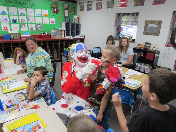 Staff photo by Cathy Spaulding<br /> Hi-Bi, a Shrine clown, engages in a nose-tweaking battle with Early Learning Center student Cooper Mahoney after Cooper snatched Hi-Bi's big red nose Monday morning. Shrine clowns visited area schools Monday to hand out tickets to this week's Bedouin Shrine Circus.
