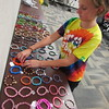 Staff photo by Cathy Spaulding<br /> Emily Miller, 11, arranges dozens of bracelets she made for the Fin and Feather Fall Festival. The festival, which runs Friday through Sunday, draws hundreds to the south shores of Lake Tenkiller.