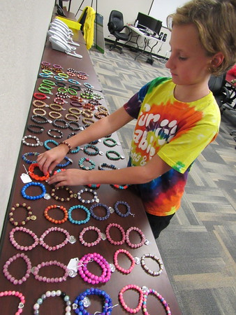 Staff photo by Cathy Spaulding Emily Miller, 11, arranges dozens of bracelets she made for the Fin and Feather Fall Festival. The festival, which runs Friday through Sunday, draws hundreds to the south shores of Lake Tenkiller.