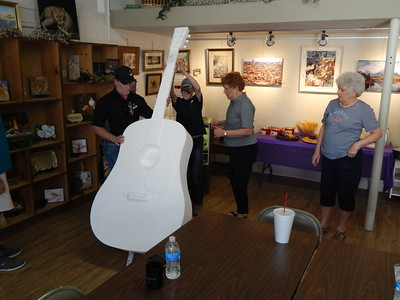 """Staff photo by Mark Hughes Kyle and Drake Vohland lift the 7-foot fiberglass acoustic guitar into its stand at the Muskogee Arts Guild on Thursday under the supervision of Wren Stratton, a member of guild. The guitars are """"version 2"""" of the Muskogee guitar project and are fashioned after the 1939 Martin Acoustic guitar. When on their platform, the guitars will stand nearly 9 feet tall. Eight of the guitars have already been purchased for $2,000. Guitars must be finished Nov. 1. Of the 19 guitars delivered, eight of them have already been purchased. Guitars are $2,000 if buyers provide their own artist or $2,500 to select one from a variety of artist's designs available at the guild."""