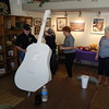 "Staff photo by Mark Hughes<br /> Kyle and Drake Vohland lift the 7-foot fiberglass acoustic guitar into its stand at the Muskogee Arts Guild on Thursday under the supervision of Wren Stratton, a member of guild. The guitars are ""version 2"" of the Muskogee guitar project and are fashioned after the 1939 Martin Acoustic guitar. When on their platform, the guitars will stand nearly 9 feet tall. Eight of the guitars have already been purchased for $2,000. Guitars must be finished Nov. 1. Of the 19 guitars delivered, eight of them have already been purchased. Guitars are $2,000 if buyers provide their own artist or $2,500 to select one from a variety of artist's designs available at the guild."