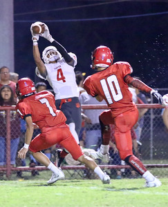 Phoenix special photo by John Hasler Fort Gibson's Rusty Rudd, center, hauls in a pass from Chandler Ladd during the Tigers' District 4A-4 opener on Friday against Stilwell.