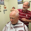 Staff photo by Cathy Spaulding<br /> Barber Dale Garrigues smoothes Dave Winn's scalp after an afternoon haircut.
