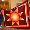Staff photo by Cathy Spaulding<br /> Shari Kamp, left, and Betty R. Martin show a star quilt being offered in a drawing at the Murrow Indian Children's Home Benefit Powwow. The annual event will be Saturday.