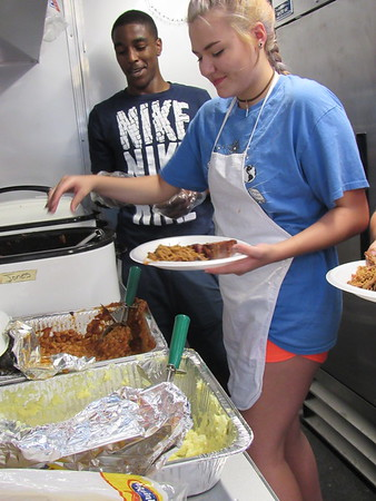 Staff photo by Cathy Spaulding<br /> Rougher Alternative Academy students Christopher Doxey and Reese Gas- saway fill plates inside a food truck. RAA's Family Career and Community Lead- ers of America members served pork and ribs during the school's parent-teacher conferences.