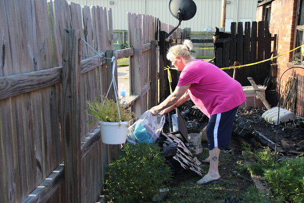 Staff photo by Harrison Grimwood<br /> Donna Fairchild collects the few items she and her roommate had that did not burn in a fire that killed one person and several pets Sunday morning.