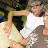 Staff photo by Cathy Spaulding<br /> Keefeton Trinity Baptist Church members Sue Lewis, left, and Judy Croftcheck scan an old church registry for members who had been baptized. Members will share memories and artifacts during Ole Timers Day on Sunday.