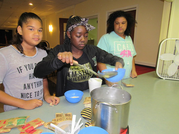 Staff photos by Cathy Spaulding<br /> Youth, from left, Keira Parker, Tiara Ryan and Ceira Parker get hot water for oatmeal during a pre-Sunday School breakfast at Antioch Church. The church is one of several that reaches to the community with  breakfasts and suppers.