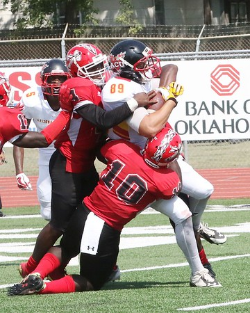 Phoenix special photo by John Hasler<br /> Bacone's Eric Brown, left, and Witherson Brutis stop Arizona Christian's Tyler Dunken near the goal goal line during the Warriors' 35-7 loss on Saturday.