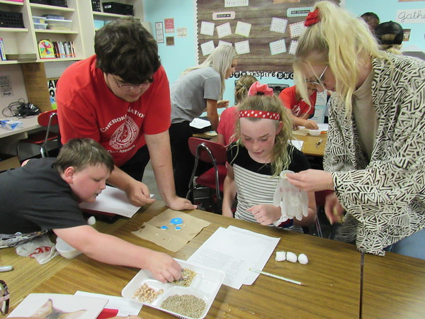 """CATHY SPAULDING/Muskogee Phoenix<br /> Fort Gibson fifth-graders and high school AP English students — from left, Kevin Patrick, Payden Kilgore, Paisley Nail and Matie Mc-Croskey — work together on a """"Garden in a Glove"""" project. The English students taught a botany lesson to the fifth-graders Friday."""