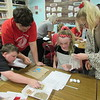 "CATHY SPAULDING/Muskogee Phoenix<br /> Fort Gibson fifth-graders and high school AP English students — from left, Kevin Patrick, Payden Kilgore, Paisley Nail and Matie Mc-Croskey — work together on a ""Garden in a Glove"" project. The English students taught a botany lesson to the fifth-graders Friday."
