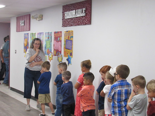 CATHY SPAULDING/Muskogee Phoenix<br /> Webbers Falls kindergarten teacher Lori Menie shushes her students during a break on their first day of school Monday. Overhead are character signs donated by Muskogee's Alice Robertson Junior High School.