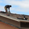 CATHY SPAULDING/Muskogee Phoenix<br /> A roofer pulls scrap material from atop the former Temple Beth Ahaba on Monday. Roofers are replacing shingles on the on the building located at 206 S. Seventh St. City Inspector Dan Hurd said the Jewish temple was sold in 2011 to JMC Development LLC.