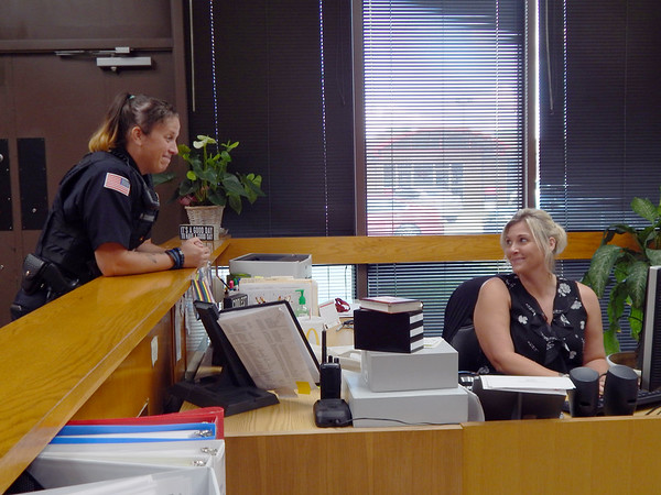 KENTON BROOKS/Muskogee Phoenix<br /> Fort Gibson police officer P.J. Oosahwee, left, talks with Fort Gibson Public Schools administrative assistant DeeDee Landers during the school day. Oosahwee has been the school's resource officer this year.