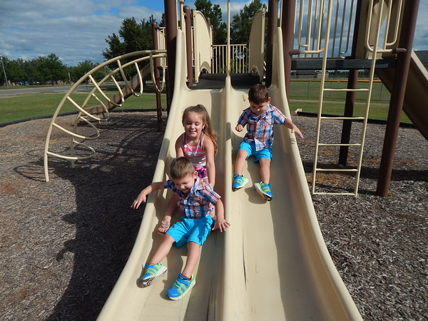 KENTON BROOKS/Muskogee Phoenix<br /> Abigail Stanley, 4, holds her brother 2-year-old Easton, while her other brother Miken, also 2, slide down the slides at the Love-Hatbox Sports Complex playground Monday. The children were enjoying the pleasant day with their parents, Paige and Raymond Stanley. The family is from Council Hill.