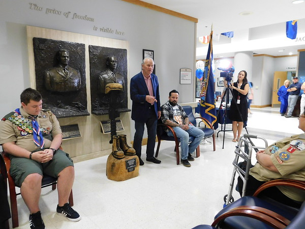 KENTON BROOKS/Muskogee Phoenix<br /> Former University of Oklahoma football coach Barry Switzer, center, talks about the battlefield cross woodcarving by his friend Anthony Marquez and donated by Tulsa Eagle Scout Mitchell Scott at Tuesday's ceremony at the Jack C. Montgomery VA Medical Center. Scott, left, presented the carving and a bench to the medical center, and Marquez, a Marine veteran, has made similar crosses for family members of 17 soldiers he fought with in Afghanistan.