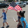 Staff photo by Cathy Spaulding<br /> Jake Conley, left, leads his Early Childhood Center schoolmates, Myla Boston, center and Raleigh Starr, across the Arrowhead Mall parking lot Monday during the ECC Patriotic Parade.