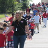 Staff photo by Cathy Spaulding<br /> Throngs of Early Childhood Center students, staff members and parents walk along Emporia Street during Monday's Patriotic Parade. The  annual parade marks the 9/11 anniversary.