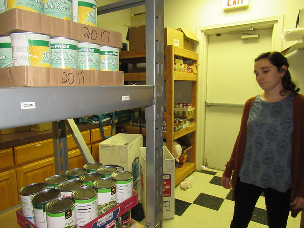 Staff photo by Cathy Spaulding<br /> Zoe Miller, secretary of First United Methodist Church, looks through the Fort Gibson Food Bank inventory. A Bed Turning benefiting the food bank will be held at Q.B. Boydstun Library.