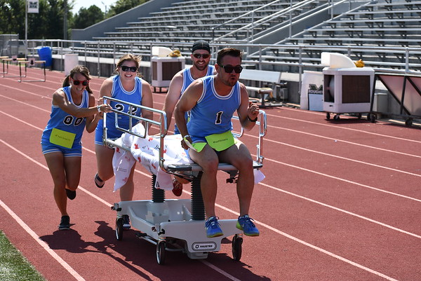Staff photo by Mark Hughes<br /> Members of team #hashtag make a mad dash to the hospital stretcher finish line. Pushing John Hasler are Andi Delmedico, Amy Hasler and Nick Delmedico.