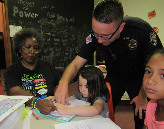 Staff photo by Cathy Spaulding<br /> Future Scholars tutor Riney Pickett and Muskogee Police officer Tyler Evans help 5-year-old Eden Hicks with her school work, while Madison Jennings, 8, looks on. Pickett tutors 18 Pershing Elementary students after school in her Future Scholars program.
