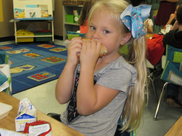 Staff photo by Cathy Spaulding<br /> Kindergartner Allison Hastings bites into a ham sandwich during a free afternoon meal at Oktaha Elementary. The school has applied for a federal food program through the Oklahoma Department of Education.