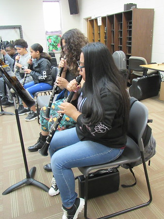 Sixth-grade band students, from right, Melody Rock and Alaira Henry practice fingering and beat during a class.