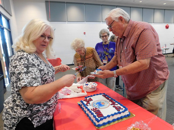 KENTON BROOKS/Muskogee Phoenix<br /> Debbie Sorenson, left, cuts cake for Carl Threlkeld at the 70th anniversary of the Muskogee-Azalea Chapter of the National Active and Retired Federal Employees Association (NARFE) celebrated Thursday at the Dr. Martin Luther King Jr. Community Center. Shirley Coker and Carl's wife Delores wait in line.