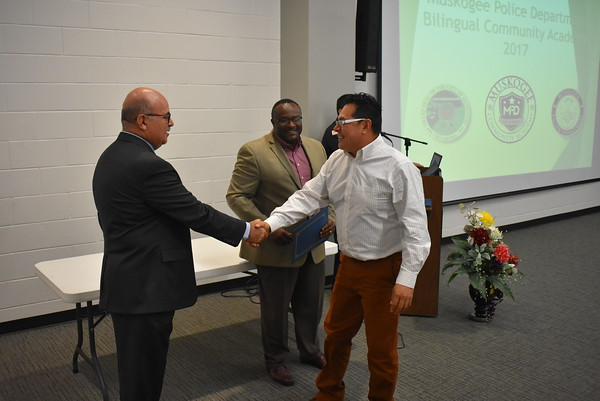 Staff photo by Mark Hughes<br /> Salvadore Coronado, right, is congratulated by the Mexican Consul Rodolfo Quilantan Arenas during a graduation ceremony Tuesday evening at the Dr. Martin Luther King Jr. Community Center. Deputy Chief of Police Reggie Cotton, who presented the certificates, looks on.