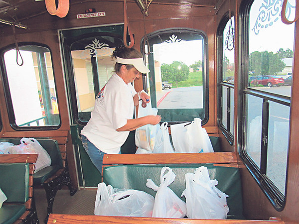 "CATHY SPAULDING/Muskogee Phoenix<br /> LeAnn Glory, administration assistant for Muskogee County Transit, loads grocery bags in back of a trolley Thursday. Muskogee County Transit Executive Director Darla Bennett said more than 37 bags of food were donated Thursday to the ""Stuff the Bus"" campaign. A Muskogee trolley was parked at the Homeland on Chandler Road. Shoppers were encouraged to donate nonperishable food items. The food will go to the Salvation Army. Bennett said some donors brought food from other stores."
