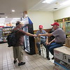 CATHY SPAULDING/Muskogee Phoenix<br /> Fred Steffen, left, takes a goody bag from First Baptist Church of Checotah volunteer Bob James, right, as Bob Vinson watches. The church leads services and distributes goody bags at the Flying J Truck Stop each Sunday.