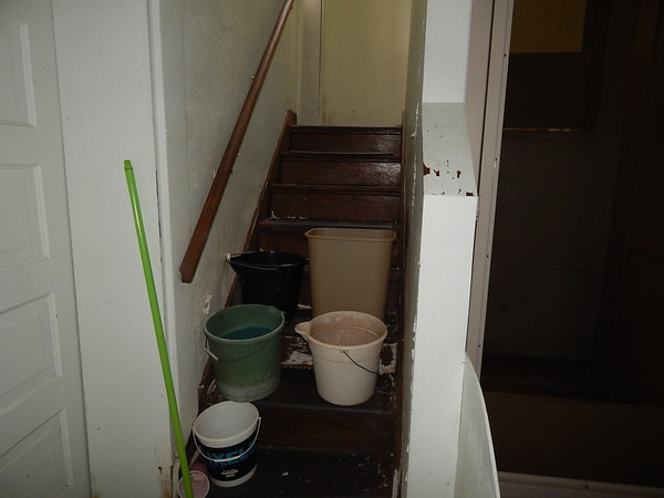 KENTON BROOKS/Muskogee Phoenix<br /> Buckets stand ready to catch water from a leaky roof on rotting stairs at the Carnegie Library in Wagoner. The library was built in 1912 and needs repairs, including the air conditioning and lights.