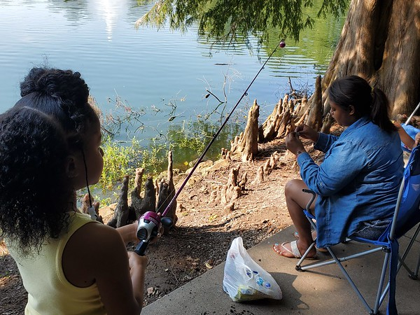 CHESLEY OXENDINE/Muskogee Phoenix<br /> Tequila Grayson affixes a worm to Kaydence Grayson's hook during Saturday's annual Fishing Derby at Honor Heights Park.