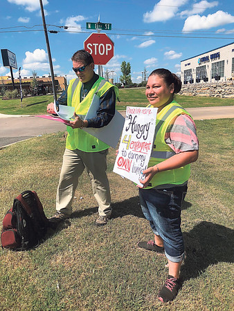 "CHESLEY OXENDINE/Muskogee Phoenix<br /> Kevin Fulkerson, left, and Kristina Escalante, right, prepare for a day of ""reverse panhandling"" — handing out resumes rather than asking for money."