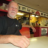 Staff photo by Cathy Spaulding<br /> Speedway Grille co-owner Mike Withrow takes a break from his work. Pictures of some of Withrow's race cars can be found on restaurant walls.