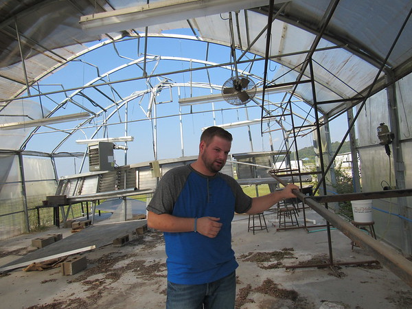 Staff photo by Cathy Spaulding<br /> Connors State College sophomore Matt Staples shows a greenhouse damaged in a May storm. The damaged greenhouse hasn't kept Connors from having its Fall Plant Sale this month.