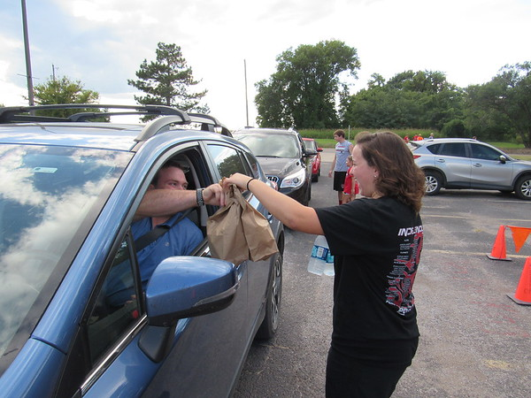 CATHY SPAULDING/Muskogee Phoenix<br /> Fort Gibson High School swim team member Jara Johnson serves two bags of barbecue sandwiches and two bottles of water to Brad Holland during the team's annual drive-through Friday night. The team has held the drive-through for 21 years.
