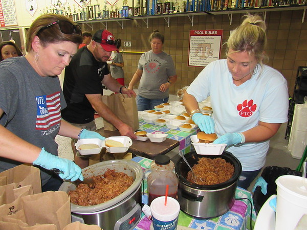 CATHY SPAULDING/Muskogee Phoenix<br /> Fort Gibson High swim team parents Dodee Hammond, left, and Deedee Landers stuff barbecued pork into sandwiches to be served at the team's annual drive-through fundraiser. The feed raises about $2,000 for the team.