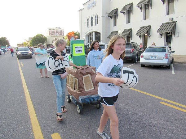 "Sixth-graders, from left, Sydney Adair, Aubrey Foster<br /> and Gabby Green proclaim the homecoming theme, ""Roughers from Coast to Coast,"" as they pull their float."