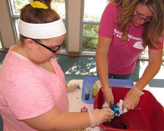 Staff photo by Cathy Spaulding<br /> Q.B. Boydstun Library clerk Abby Jackson, right, helps Megan Walters dye her T-shirt during the library's tie-dye program Friday. Five visitors took a hippy, drippy trip to the 1960s when Q.B. Boydstun Library hosted a tie-dye T-shirt session. Visitors wrapped their shirts and bound them in rubber bands. They then squirted different colors of dye into the cloth bundles. Some drew a heart on the front of their shirts. Jackson said participants put their bundles in plastic bags and took them home to dry. Once dry, the shirts had colorful patterns.