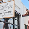 Staff photo by Mark Hughes<br /> Jeff Goodnight, with Jones Aluminum, prepares a brace on the awning over Poppy's Garden at 200A S. Main St.